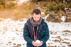 Mann, der mit dem Schnee spielt snowball Lizenzfreie Stockfotos