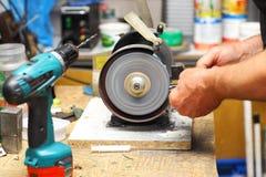 Mann, der mit dem Schärfen der Werkzeugmaschine arbeitet Lizenzfreie Stockfotos