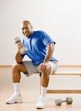 Mann, der mit Dumbbells im Gesundheitsklumpen ausarbeitet Stockfotos