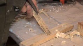 Mann, der mit einem Meißelholzklotz arbeitet stock video