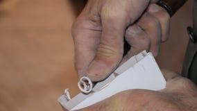 Mann, der mit einem Meißelweißplastik arbeitet stock video footage