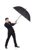 Mann, der mit einem Regenschirm kämpft lizenzfreie stockfotos