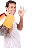 Mann, der mit Einkaufstaschen lächelt Lizenzfreies Stockfoto