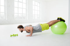 Mann, der mit fitball trainiert Stockfotos