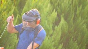 Mann, der mit Grastrimmer arbeitet stock video footage