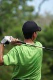 Mann, der mit grünem Hemd Golf spielt Stockbild