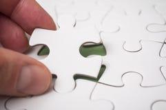 Mann, der mit der Hand das letzte Stück des Puzzlen auf den grünen Hintergrund, zum des Auftrags abzuschließen setzt stockbild