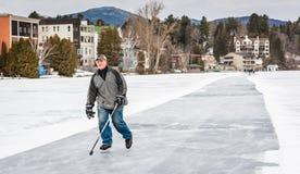 Mann, der mit Hockeyschläger eisläuft Stockbild