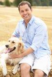 Mann, der mit Hund auf Stroh-Ballen in geerntetem F sitzt Lizenzfreies Stockbild