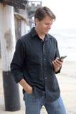 Mann, der mit intelligentem Telefon am Strand sich verständigt Lizenzfreie Stockfotografie