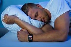 Mann, der mit intelligenter Uhr in seiner Hand schläft lizenzfreie stockbilder