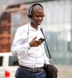 Mann, der mit Kopfhörern in der Stadt geht stockfoto