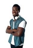 Mann, der mit Kopfhörern um seinen Stutzen steht Stockbild