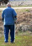 Mann, der mit Krückeen in der landwirtschaftlichen Einstellung geht Stockfotos