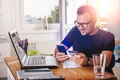 Mann, der mit Kreditkarte am intelligenten Telefon zahlt Stockfotografie