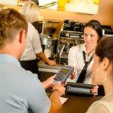 Mann, der mit Kreditkarte am Kaffee zahlt Lizenzfreie Stockbilder