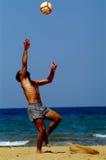Mann, der mit Kugel auf Strand spielt Lizenzfreie Stockfotos