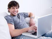 Mann, der mit Laptop arbeitet Stockfotografie