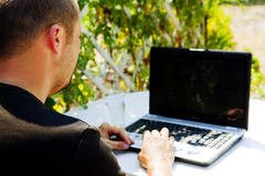 Mann, der mit Laptop draußen arbeitet Stockfoto