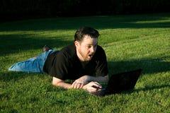 Mann, der mit Laptop im Park arbeitet Lizenzfreies Stockfoto