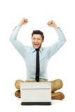 Mann, der mit Laptop mit den Armen angehoben sitzt Lizenzfreie Stockfotografie