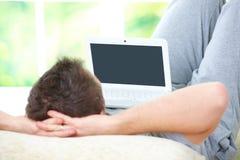 Mann, der mit Laptop sich entspannt Stockfoto