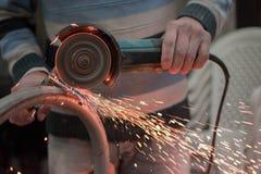 Mann, der mit Metallschleifer arbeitet stockbilder