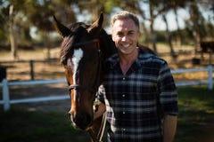 Mann, der mit Pferd in der Ranch steht stockbild