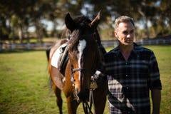 Mann, der mit Pferd in der Ranch steht lizenzfreies stockfoto