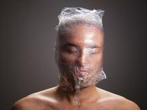 Mann, der mit Plastik um seinen Kopf erstickt lizenzfreie stockfotografie