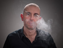 Mann, der mit Rauche in seinem Gesicht raucht Stockbilder