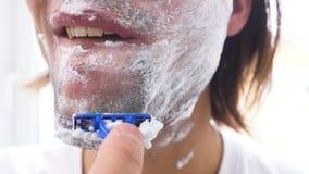 Mann, der mit Schaum und manuellem razer sich rasiert stock video