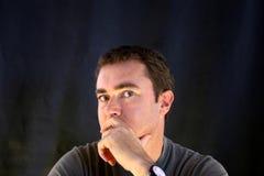 Mann, der mit schwarzem Hintergrund denkt Stockbild