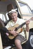 Mann, der mit seinem Hund beim Spielen der Gitarre in RV sitzt stockfotos