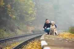 Mann, der mit seinem Hund mit dem Zug reist Lizenzfreies Stockfoto