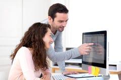 Mann, der mit seinem Mitarbeiter auf Computer arbeitet Lizenzfreies Stockfoto
