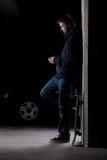 Mann, der mit Skateboard steht Stockfotografie