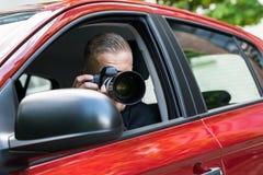 Mann, der mit slr Kamera vom Auto fotografiert Stockbilder