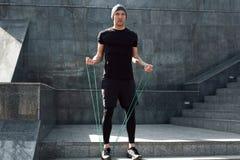 Mann, der mit springendem Seil aufwärmt stockfoto