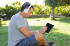 Mann, der mit Tabletten-PC sich entspannt Stockfotografie