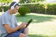 Mann, der mit Tabletten-PC sich entspannt Lizenzfreie Stockfotos
