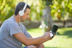 Mann, der mit Tabletten-PC sich entspannt Stockbilder