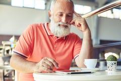 Mann, der mit Tasse Kaffee- und Tabletten-PC sich entspannt Stockfotos