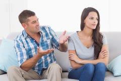 Mann, der mit verärgerter Frau auf Sofa argumentiert Lizenzfreie Stockfotos