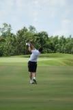 Mann, der mit weißem Hemd Golf spielt Stockbild