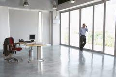 Mann, der Mobiltelefon gegen Glaswand im leeren Büro verwendet Stockfoto