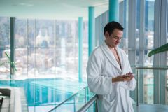 Mann, der Mobiltelefon nahe Innenswimmingpool verwendet lizenzfreie stockfotografie