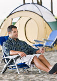 Mann, der MP3-Player am Campingplatz verwendet Stockfotos