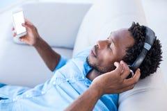Mann, der Musik bei der Entspannung auf Sofa genießt Stockbilder