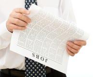 Mann, der nach Job im Papier - Nahaufnahme sucht stockfotografie